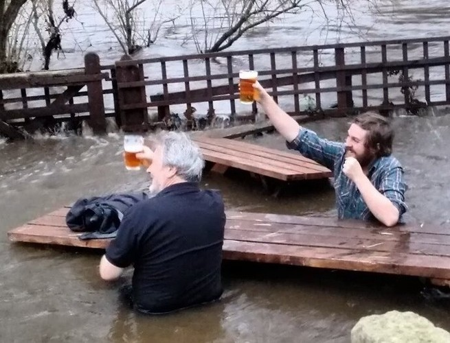 Two Guys Keep Drinking In Flooded Beer Garden